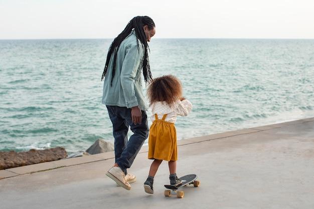 Полный кадр отец и девочка на берегу моря