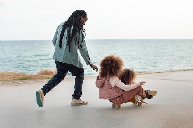 海辺でフルショットの父と子供たち