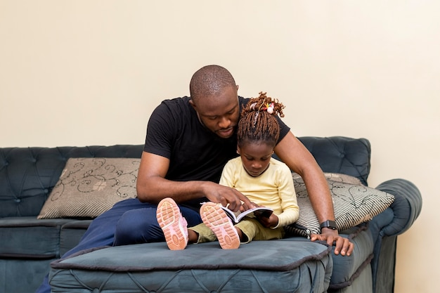 Full shot father and girl on couch