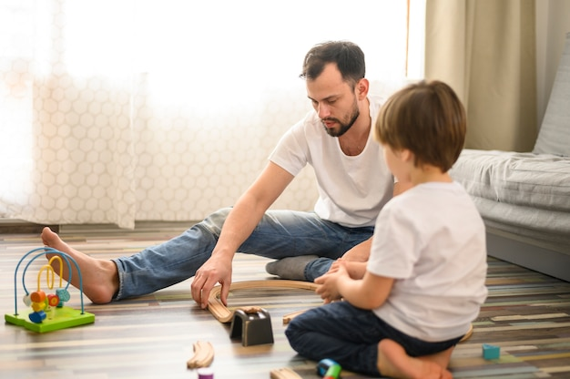 Full shot father playing with son on floor