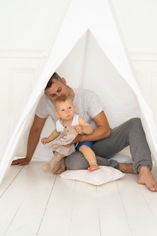 Full shot father sitting with baby boy under tent