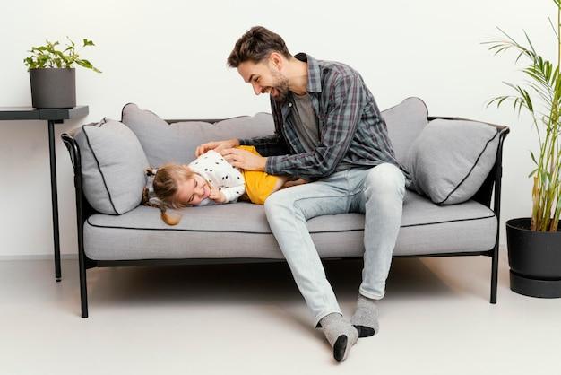 Full shot father tickling girl