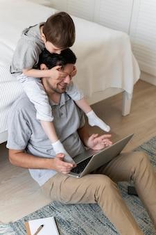 子供と一緒に床で働くフルショットの父