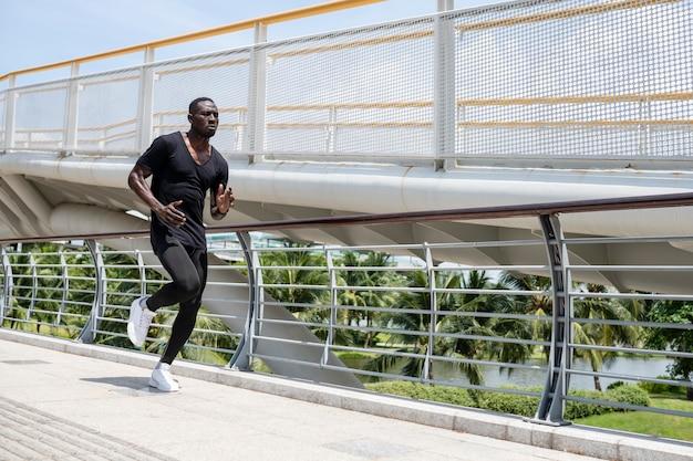Uomo in forma di colpo pieno che corre all'aperto