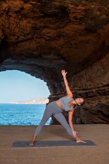Donna in forma a tutto campo che fa posa yoga in riva al mare