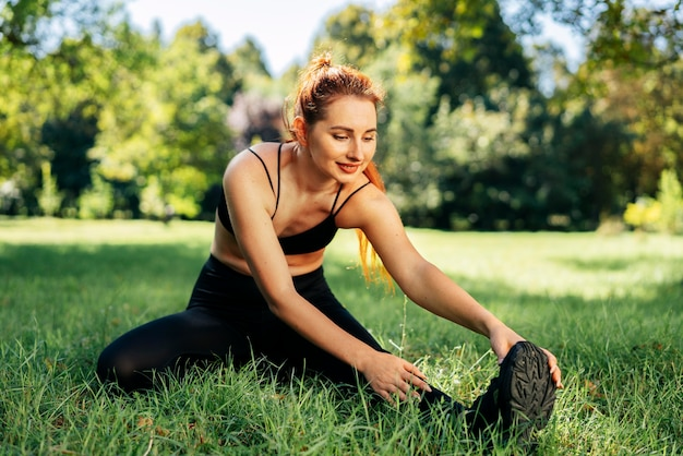 Full shot fit woman exercising on grass