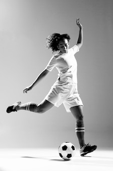 Full shot fit woman kicking ball