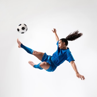 Full shot fit woman kicking ball