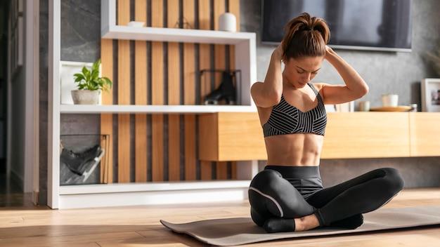Donna adatta del colpo pieno sulla stuoia di yoga