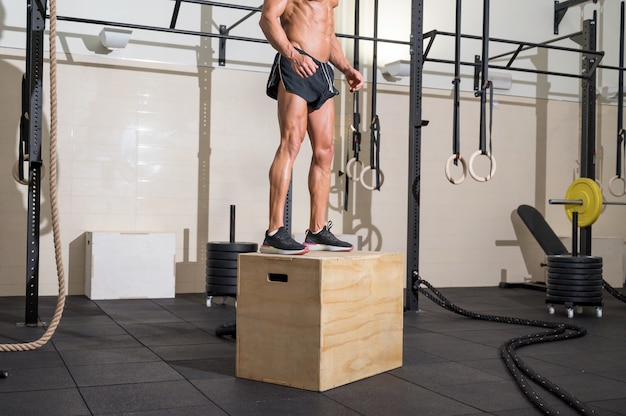 Full shot of a fit young caucasian sportsman training alone doing box jump exercise in the gym
