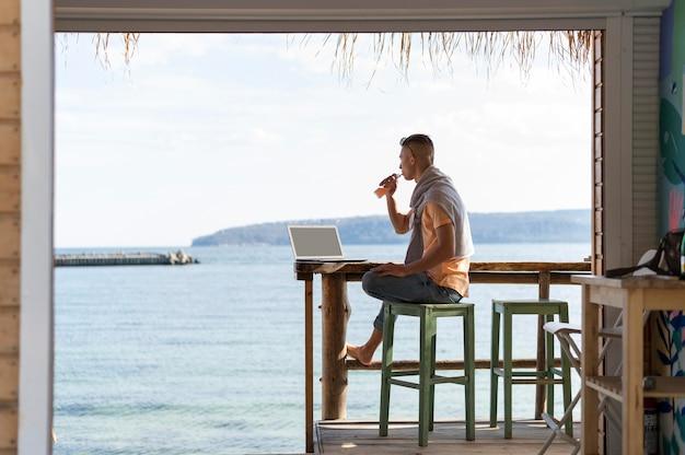 Full shot freelancer at seaside