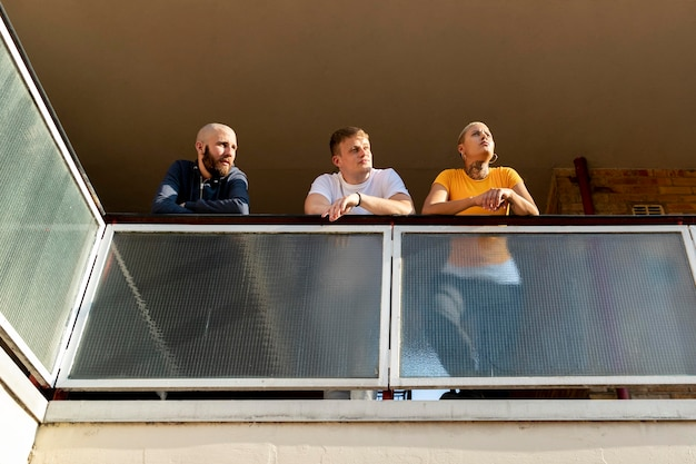 Full shot friends on balcony