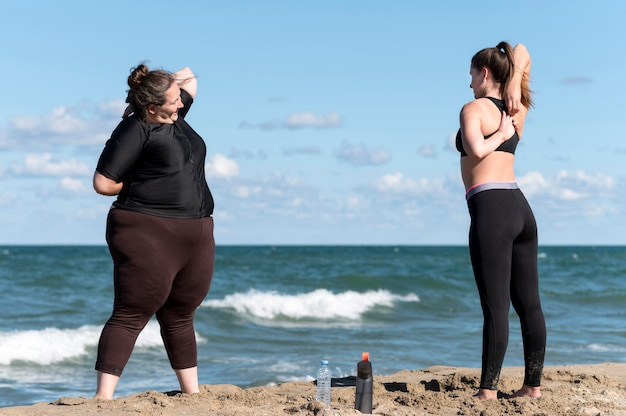 Полный снимок друзей, занимающихся спортом на пляже