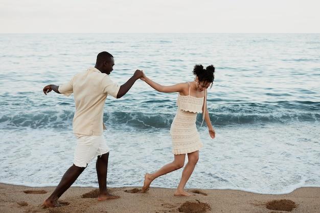 해변에서 손을 잡고 있는 전체 샷 친구