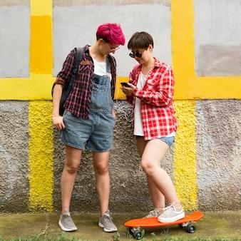 Amici della foto a figura intera che esaminano smartphone