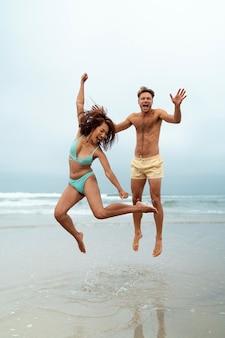 Полный снимок друзей, позирующих на пляже