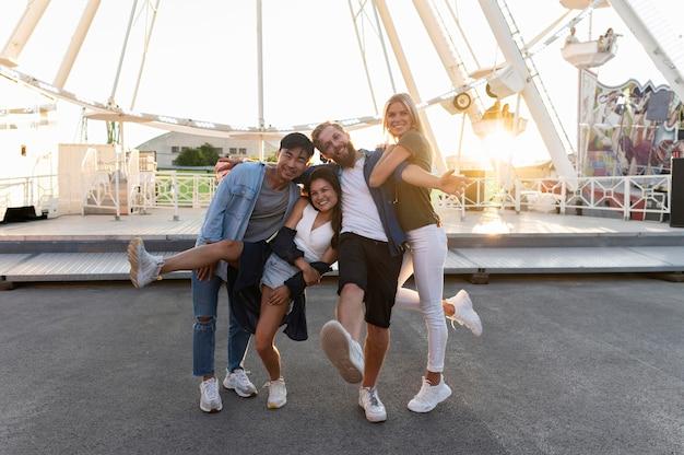 Full shot friends posing at funfair