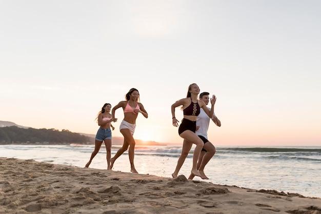 Full shot friends running on beach