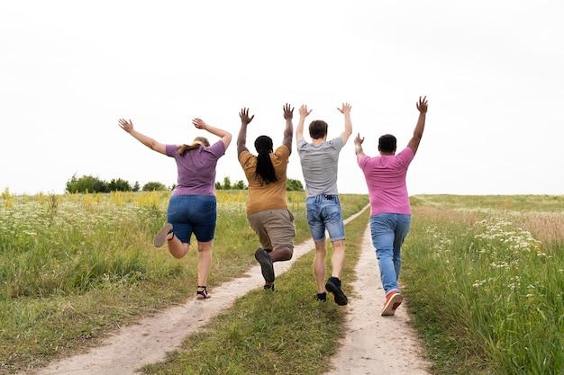 Full shot friends running outdoors