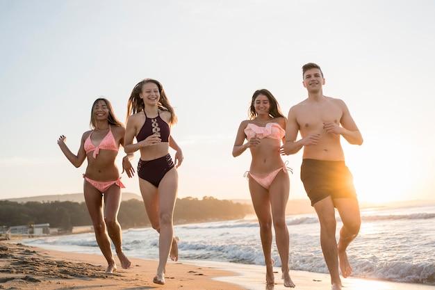 Full shot friends running on shore