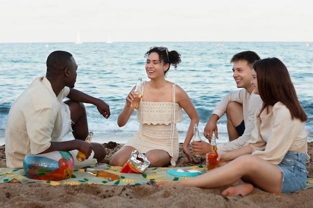 Amici a tutto campo seduti sulla spiaggia
