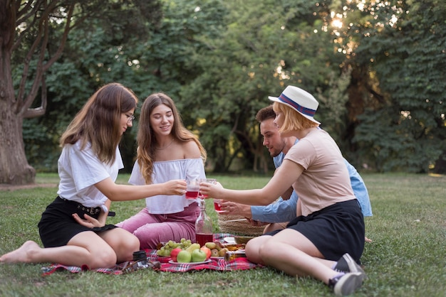 Full shot friends sitting on cloth outdoors