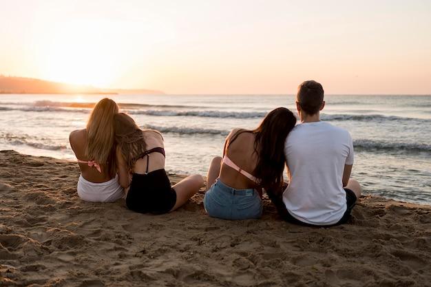 Полный выстрел друзей, сидя на пляже