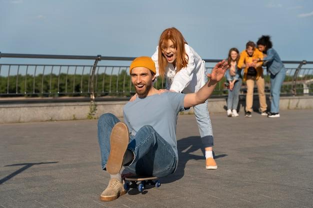 Полный кадр друзей со скейтбордом
