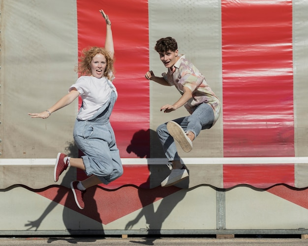 Full shot funny couple jumping together