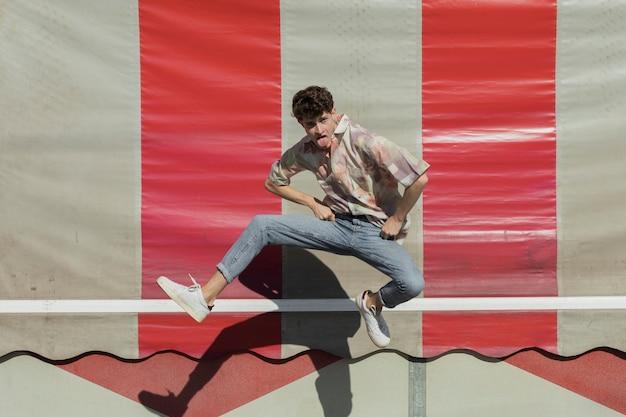 Full shot funny guy jumping outdoors