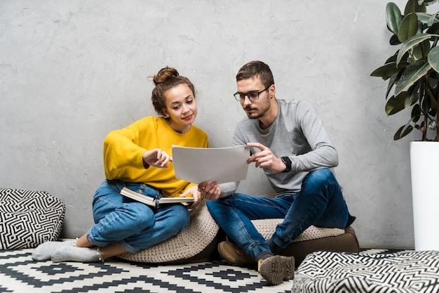 Полный снимок девочка и мальчик читают что-то