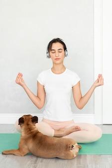 Полный снимок девушка и собака на коврике для йоги