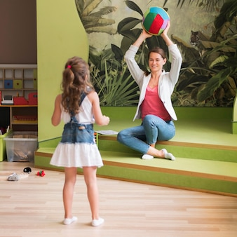 フルショットの女の子と先生が一緒に遊んで