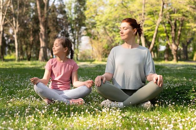 Полный снимок девушка и женщина, сидящая на траве