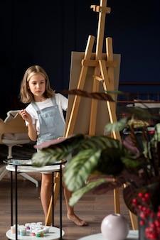 Девушка в полный рост, будучи художником