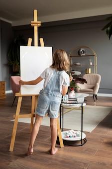 Ragazza a tutto campo che è creativa a casa