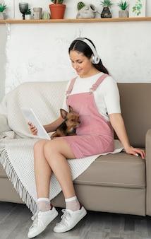 Ragazza del colpo pieno sul divano con tablet e cane