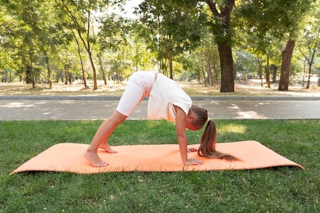 Девушка в полный рост занимается йогой на коврике
