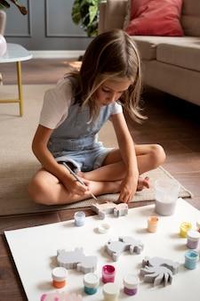 Full shot girl on floor painting