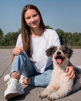 愛らしい犬を抱いたフルショットの女の子