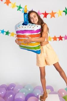 ケーキ風船を保持しているフルショットの女の子