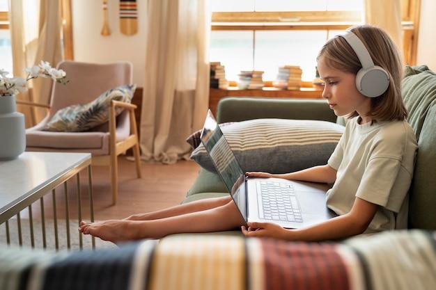 Full shot girl holding laptop at home