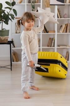 Full shot girl holding luggage