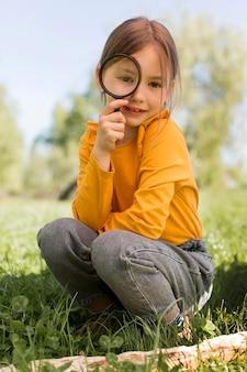 Magnigyingガラスを保持しているフルショットの女の子