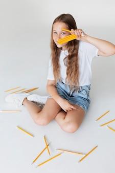 Ragazza a tutto campo con in mano le matite