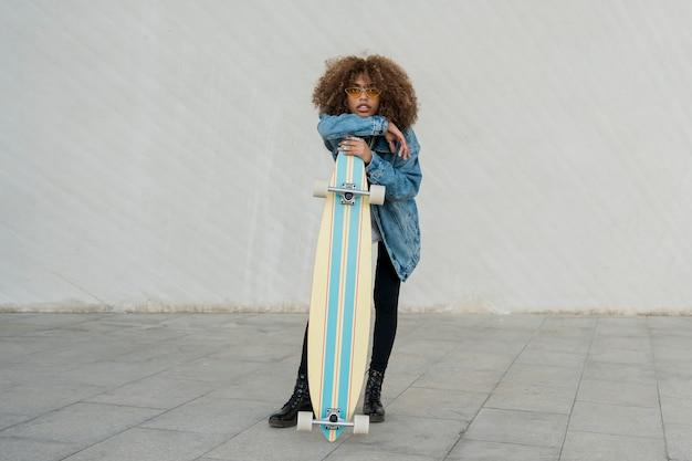 Full shot girl holding skateboard