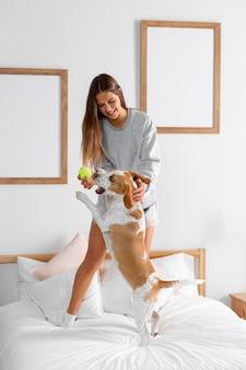 子犬と一緒にベッドでフルショットの女の子