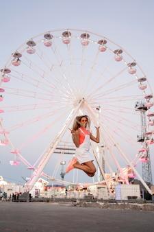 Девушка в полный рост прыгает на ярмарке