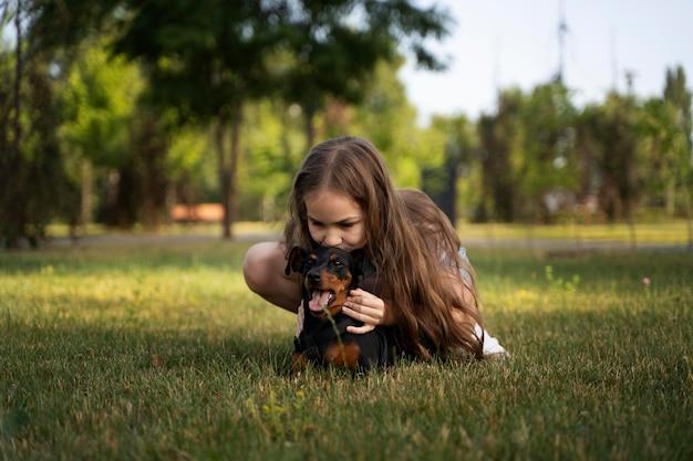 Ragazza a tutto campo che bacia il cane sulla testa