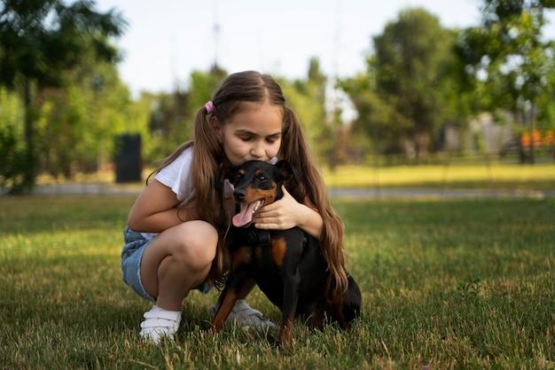 Ragazza a tutto campo che bacia cane